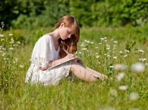 Eine junge, hübsche Frau schreibt auf einer sommerlichen Wiese/A student takes notes on a summer meadow